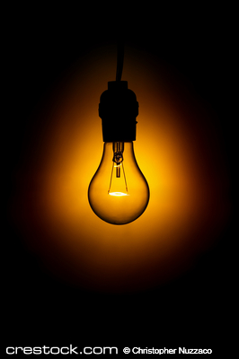 Glowing light bulb against black background.