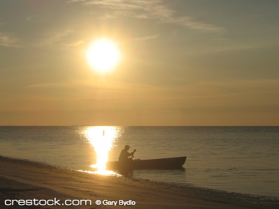 Fisherman in boat at sunrise